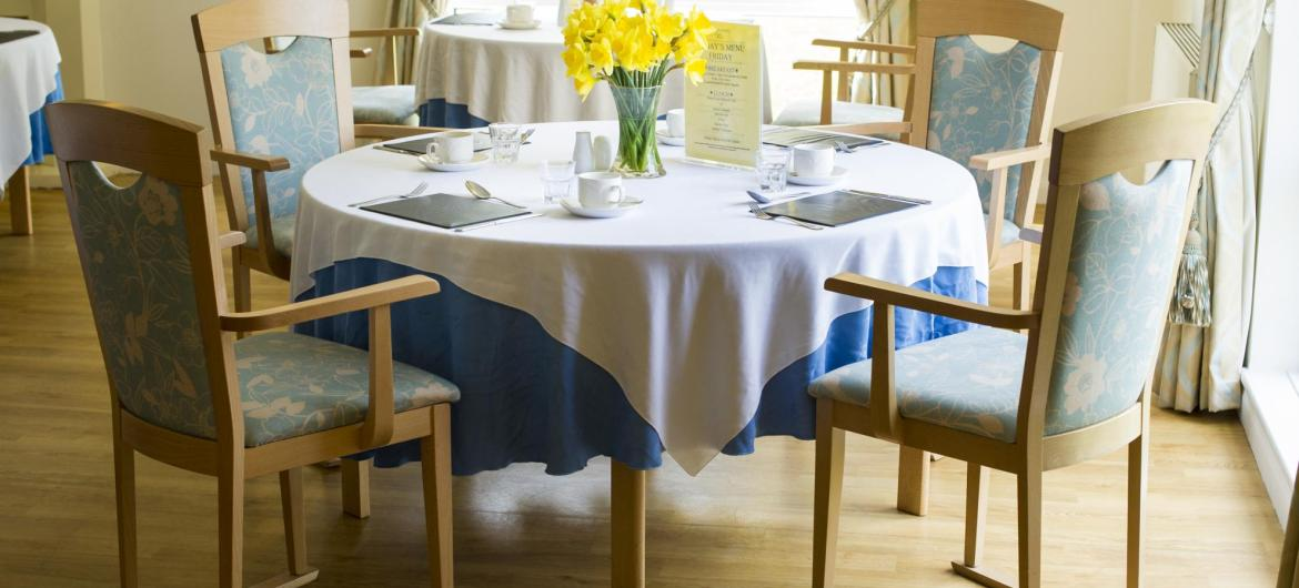 The dining room at Rowanweald Nursing Home set for lunch with table cloths and flowers.