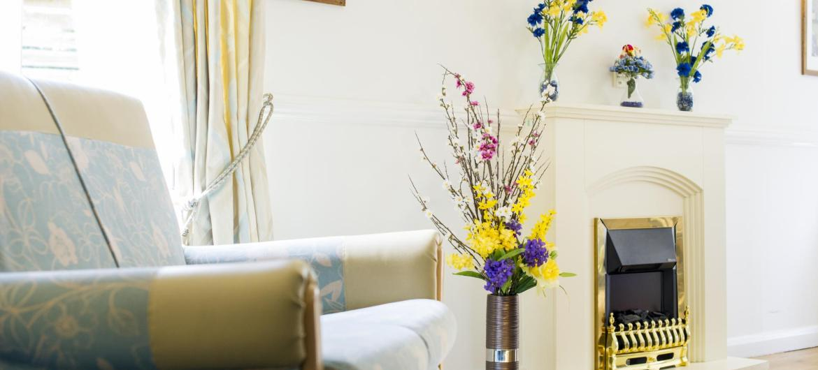 The light and bright lounge at Rowanweald Nursing Home has wooden floors and open fire place.