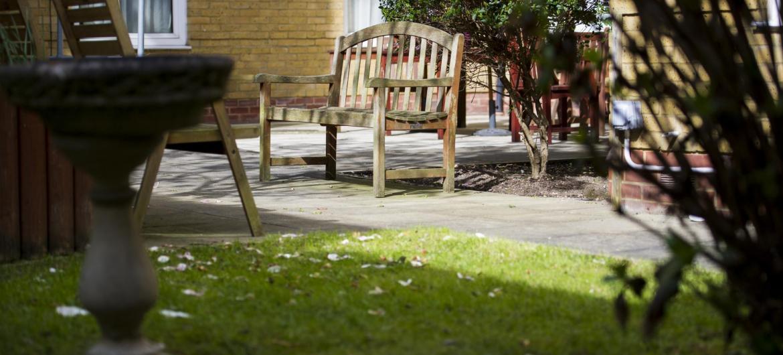 A bench in the back garden at Rowanweald Nursing Home.