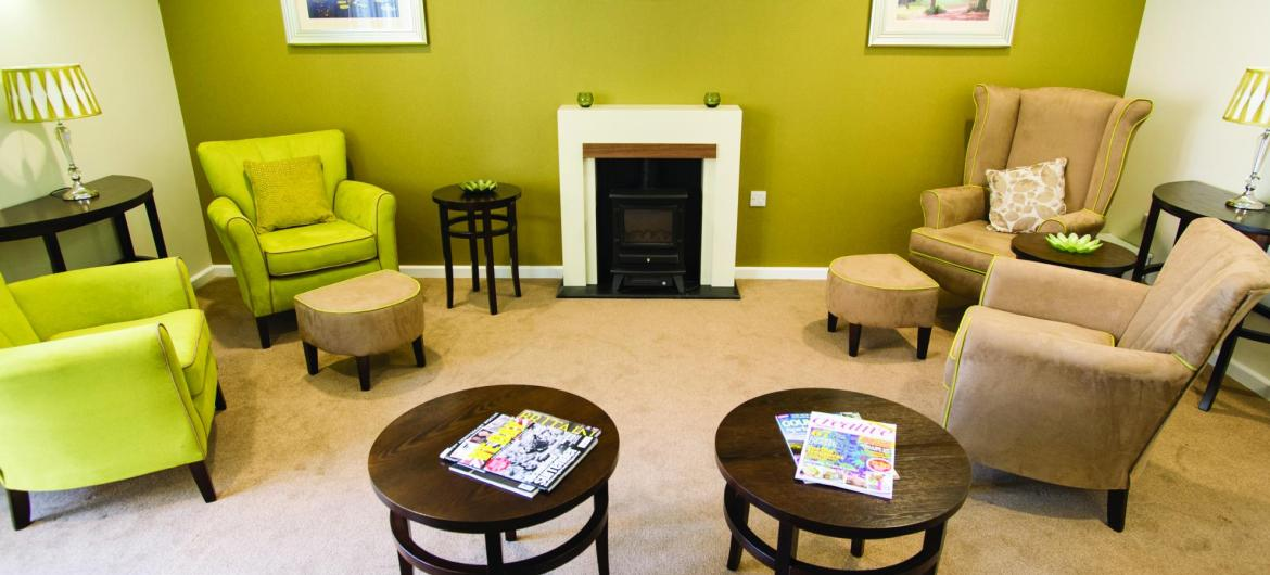 The lounge area in the Juniper House Residential Care Home with contemporary furnishings and an open fire.