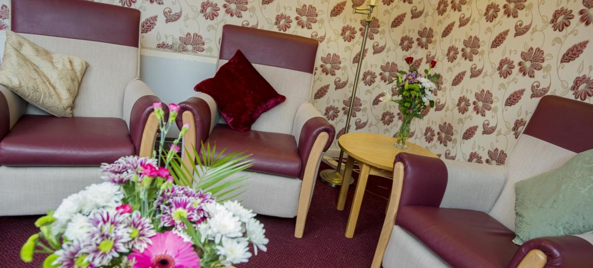 The lounge at Pinewood Residential Care Home with soft chairs, flowers and soft lighting.
