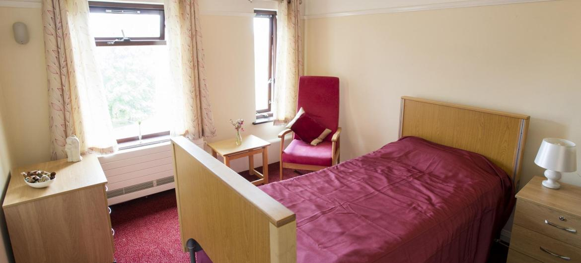 A red bedroom at Lyons Court Residential Care Home.