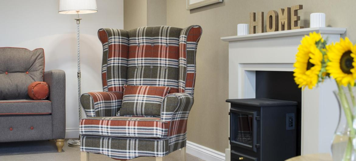 A cosy lounge with a log burning stove at Meadow View Residential Care Home.