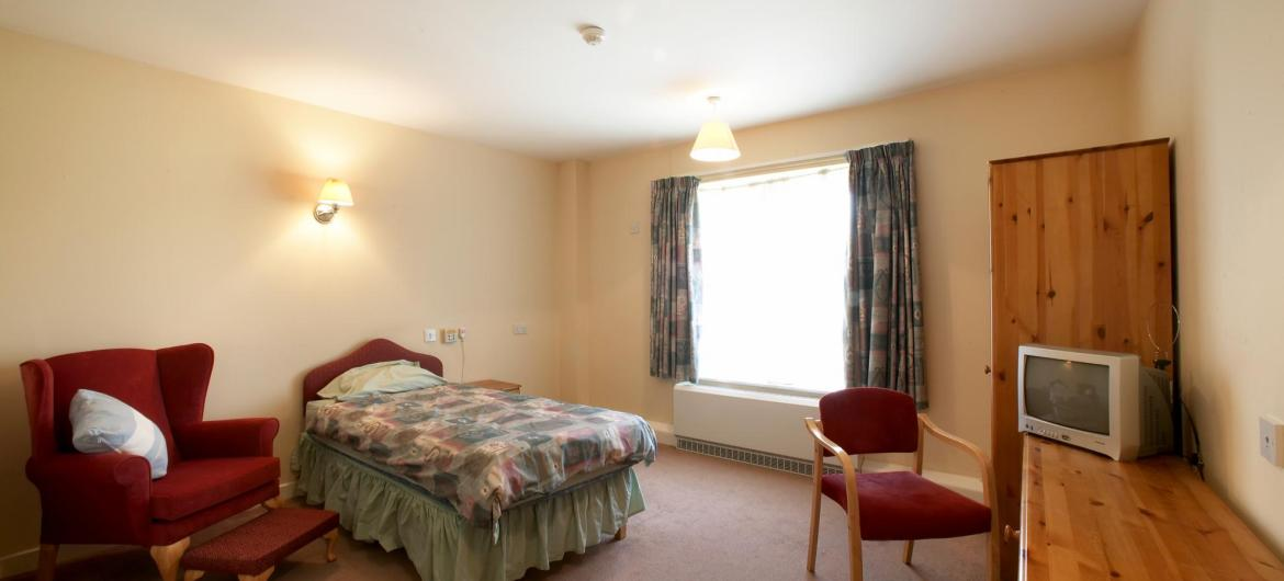A large bedroom with comfy chair and matching wooden furniture at Meadows House Residential and Nursing Home.