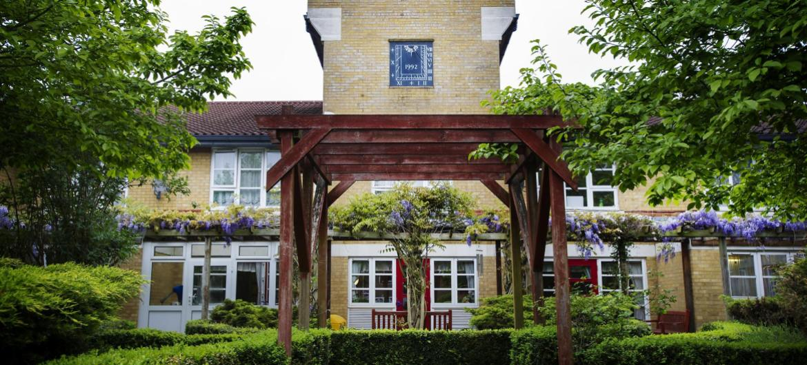 A pergola frames the exterior of Aashna House Care Home in London.