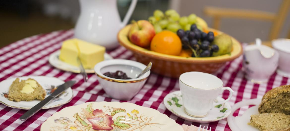 A table set for breakfast with fruit, toast and butter.