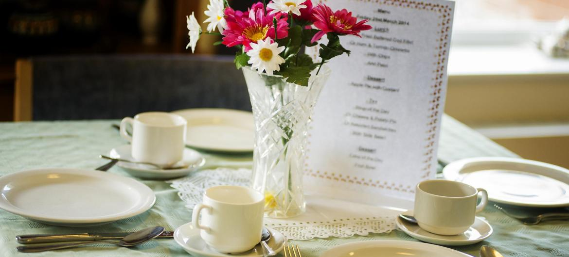 A dining table Breme Residential Care Home set with table cloth, menu and flowers.