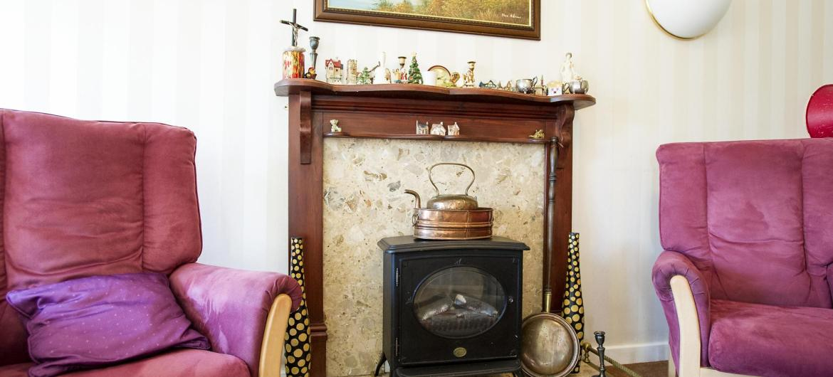Cosy lounge with cast-iron style electric stove fire at Breme Residential Care Home
