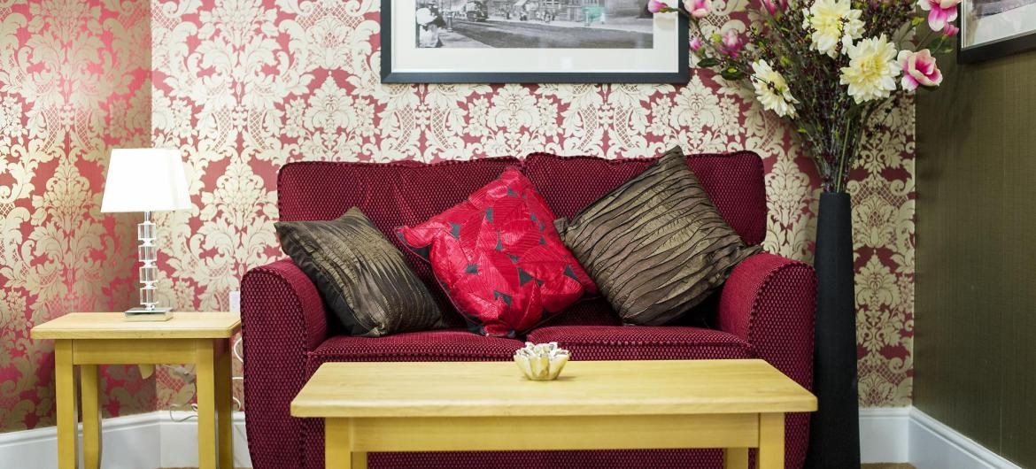 A red sofa and coordinating cushions at Castlecroft Residential Care Home.