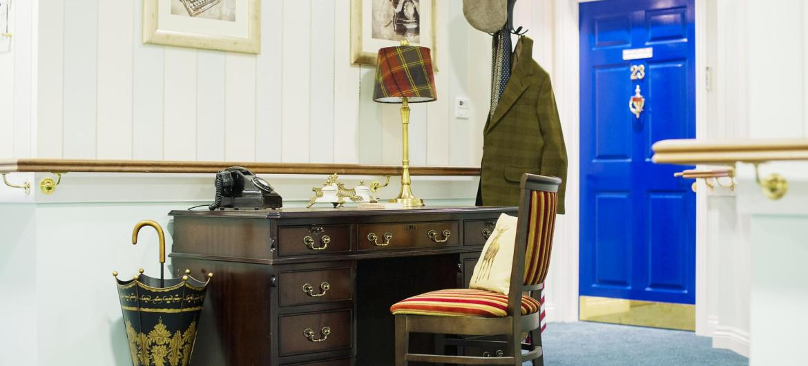 A reminiscence station in a spacious hallway with a writing desk, clothes and traditional telephone.