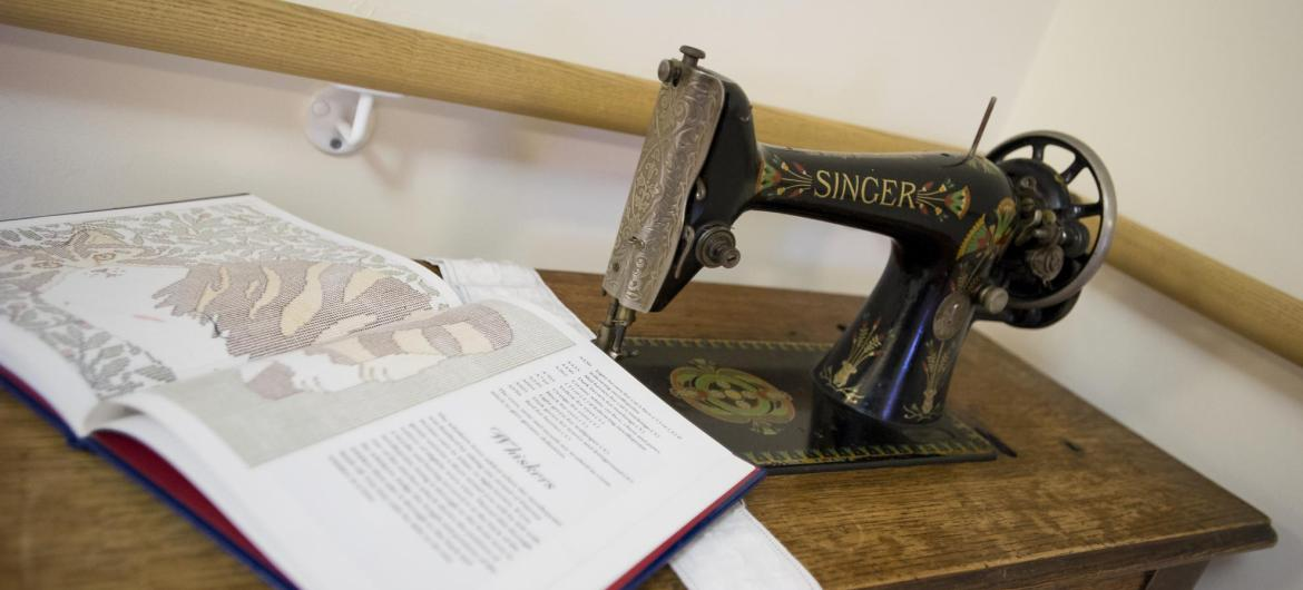 An antique book and traditional sewing machine.