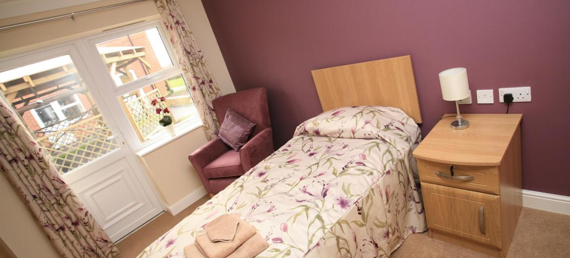 A lovely bedroom at Briarscroft Residential Care Home with door to garden area.