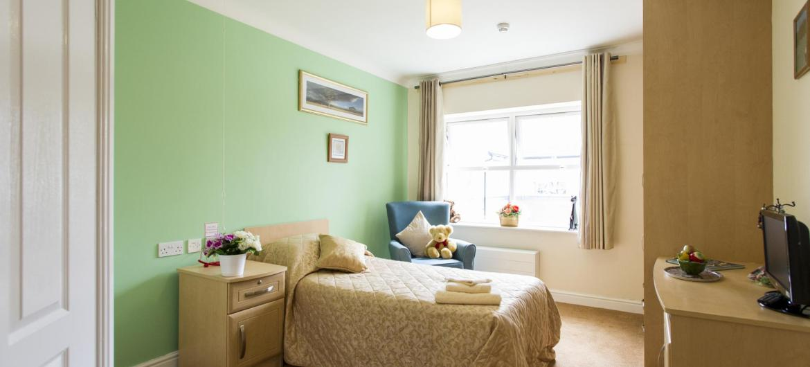 A pretty green bedroom at East Park Court Residential Care Home.