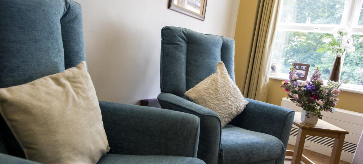 Comfy high back chairs with soft cushions in the lounge at East Park Court Residential Care Home.