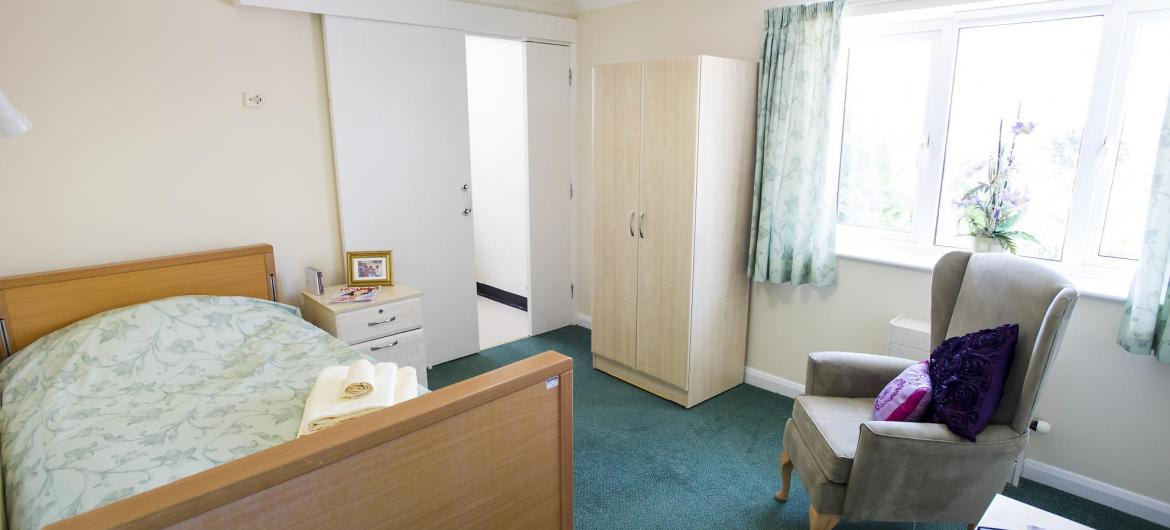 A large and airy bedroom with en-suite at the Fernihurst Nursing Home.
