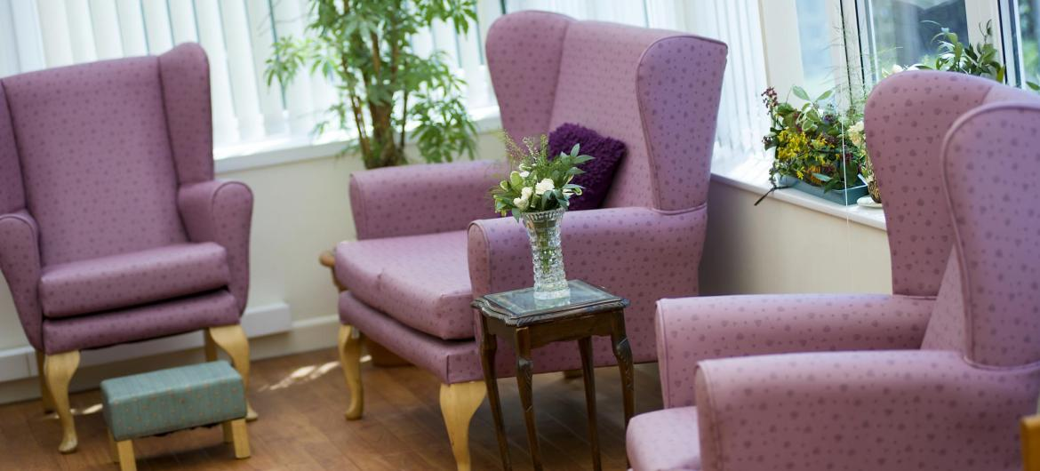 The lounge with flowers, comfy chairs and foot stools at Fernihurst Nursing Home.