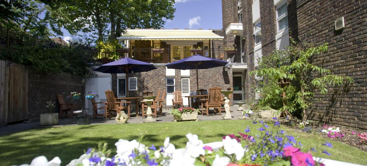 Tables, chairs and umbrellas in the pretty back garden at Forest Dene Residential Care Home.
