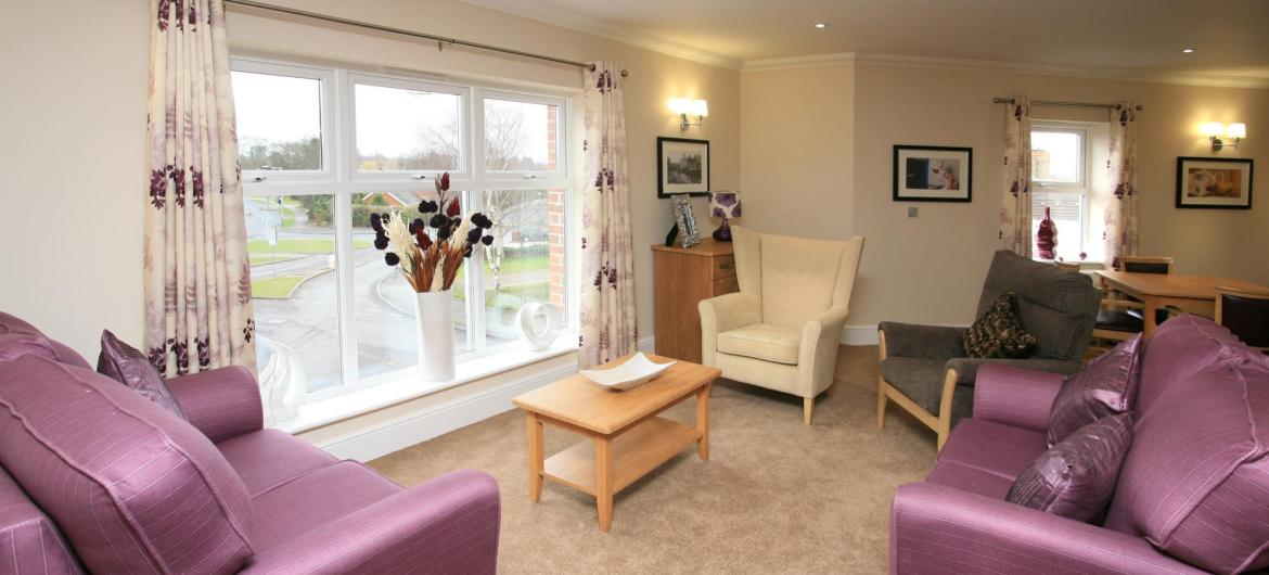 The light and airy lounge at Highcroft Hall Residential Care Home with comfy sofas, flowers and soft lighting.
