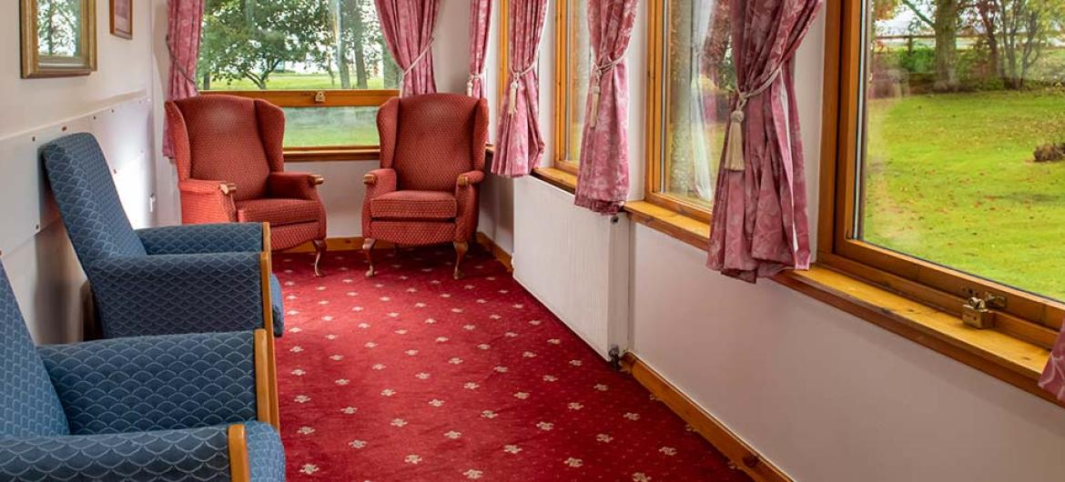 Warm and cosy seating area overlooking the landscaped gardens at Mull Hall Care Home in Invergordon