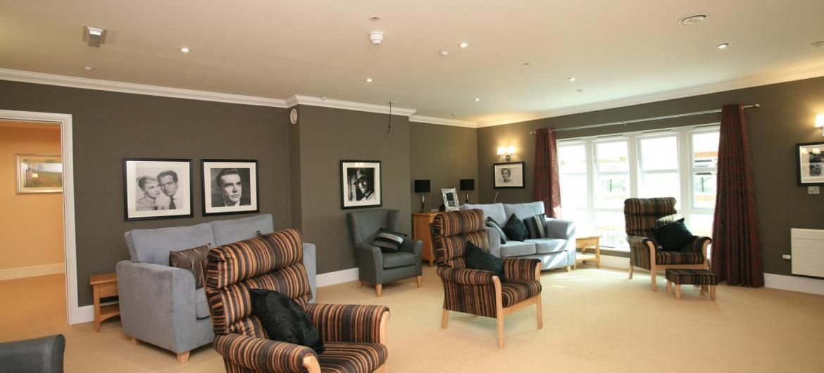 The large lounge at Park View Residential Care Home has stylish black and gold furnishings and soft down lights.