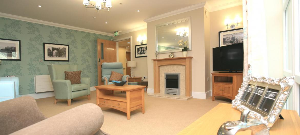 The lounge at Park View Residential Care Home has pastel toned furniture and decor.