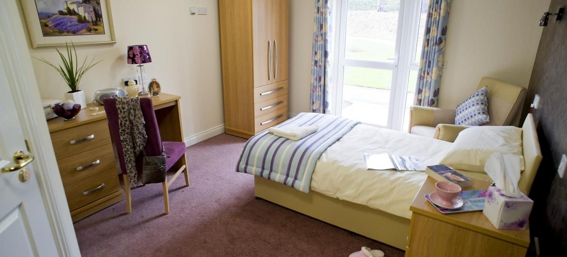 A stylish bedroom at Yarnton Residential and Nursing Home with coordinating wooden furniture.