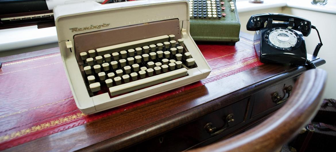 A typewriter and traditional telephone on a leather topped desk.