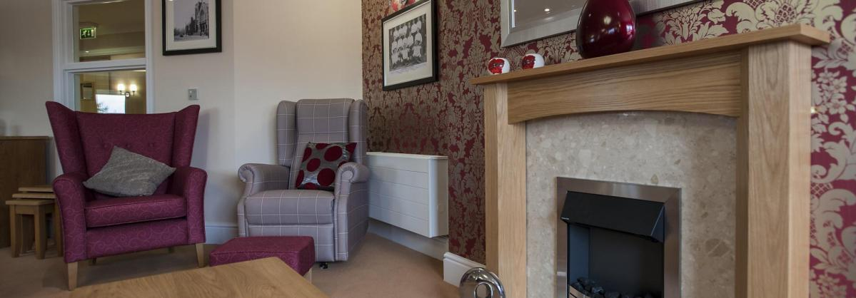 The beautiful open fire and comfortable chairs in the lounge at Lime Tree Court Residential Care Home.