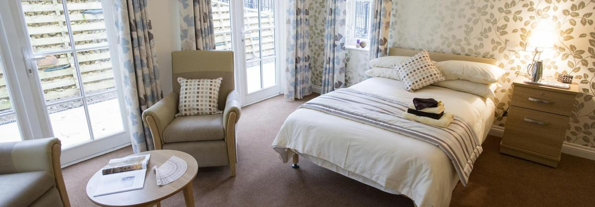 The designer-styled bedroom at Iffley Residential and Nursing Home has full length windows and soft lighting.
