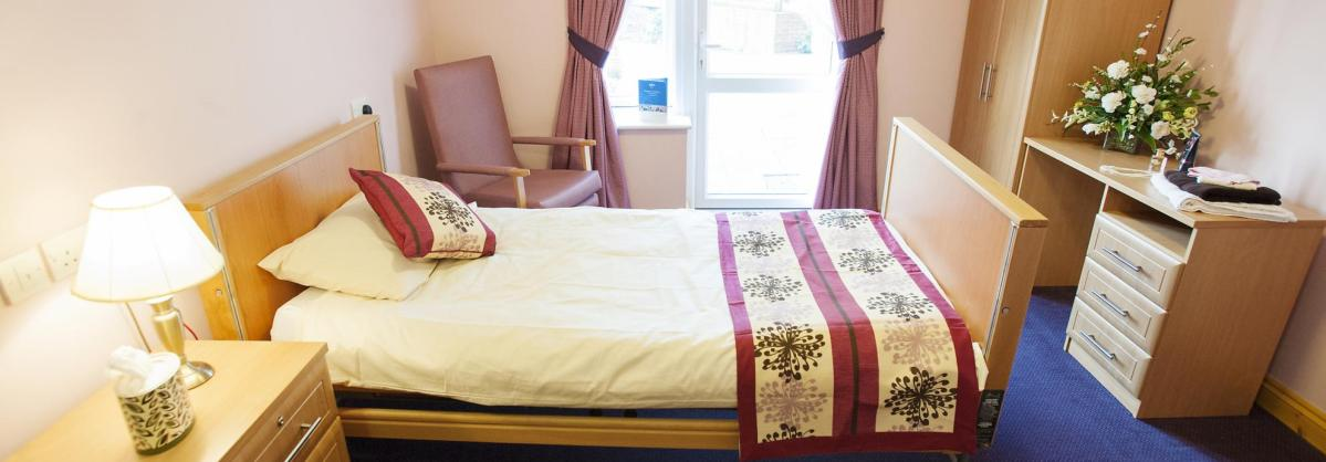 A stylish bedroom at Wantage Nursing Home with pretty throw, cushions and curtains.