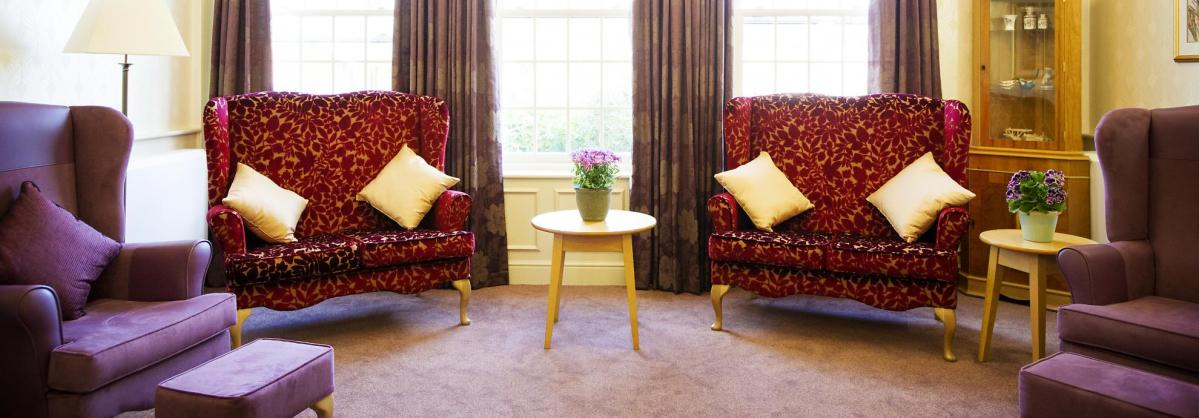 The traditionally styled lounge at Watlington and District Nursing Home has comfy chairs, cushions and side tables with flowers.