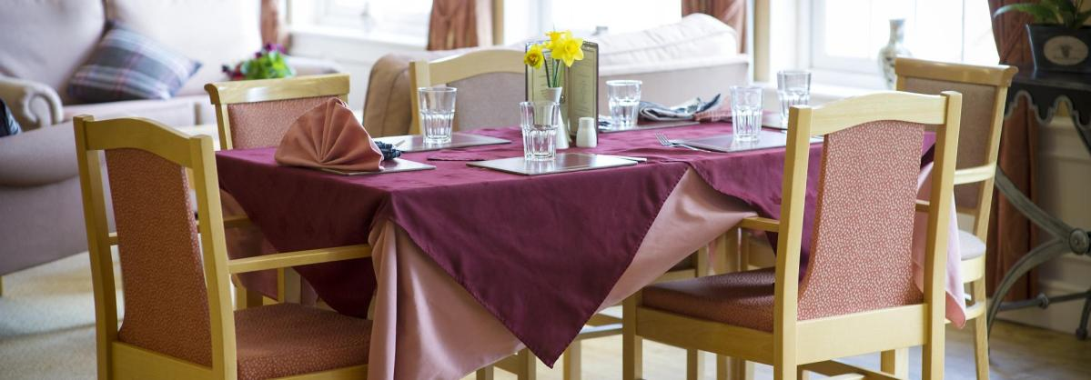 The dining room table at Watlington and District Nursing Home set for dinner with coordinating table cloths.