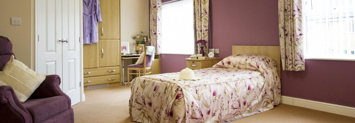A light and airy bedroom with fitted wardrobes at The Beeches Residential Care Home.