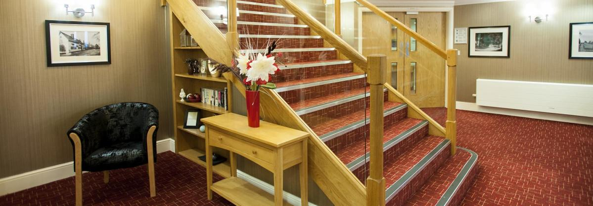 The large and welcoming reception at The Beeches Residential Care Home has a stunning glass and wooden staircase.