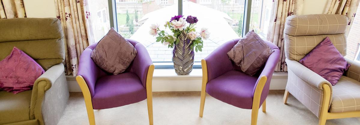 The light and bright lounge at Redhill Court Residential Care Home has bright purple chairs and matching cushions.