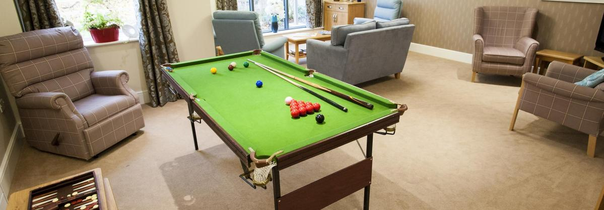 The lounge at Redhill Court Residential Care Home with a snooker table and comfy chairs.