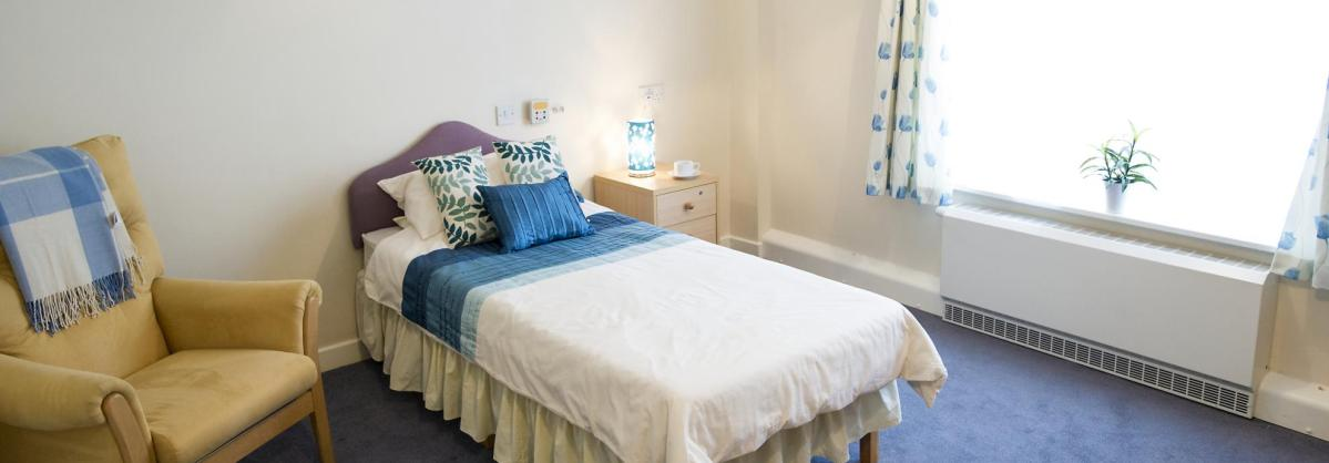 A pretty blue and white bedroom at Time Court Residential and Nursing Home.