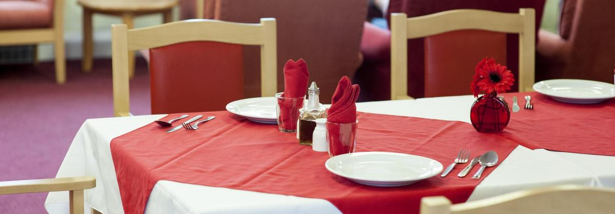 The dining room table at Time Court Residential and Nursing Home set with red and white coordinating tableware.