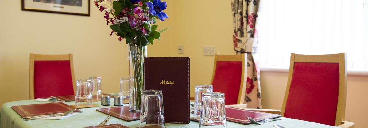 A vase of flowers and a menu are centered on the set dining table at the Manse.