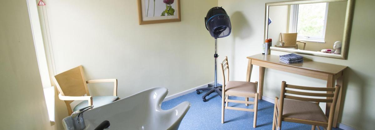 The hair dressing salon with sink, seats and mirrors at The Manse Residential Care Home.