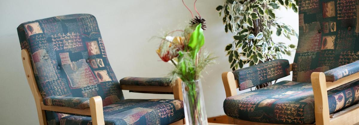 The lounge is furnished with comfy seats, tables and fresh cut flowers at the Manse Residential Care Home.