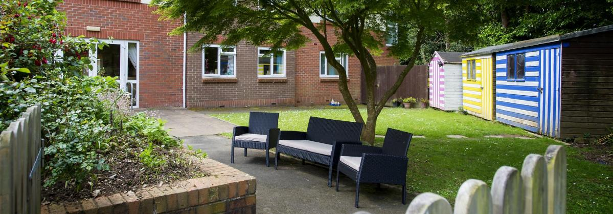 Comfy garden seats with cushions in front of colourful stripy sheds at the Ivydene Residential and Nursing Home