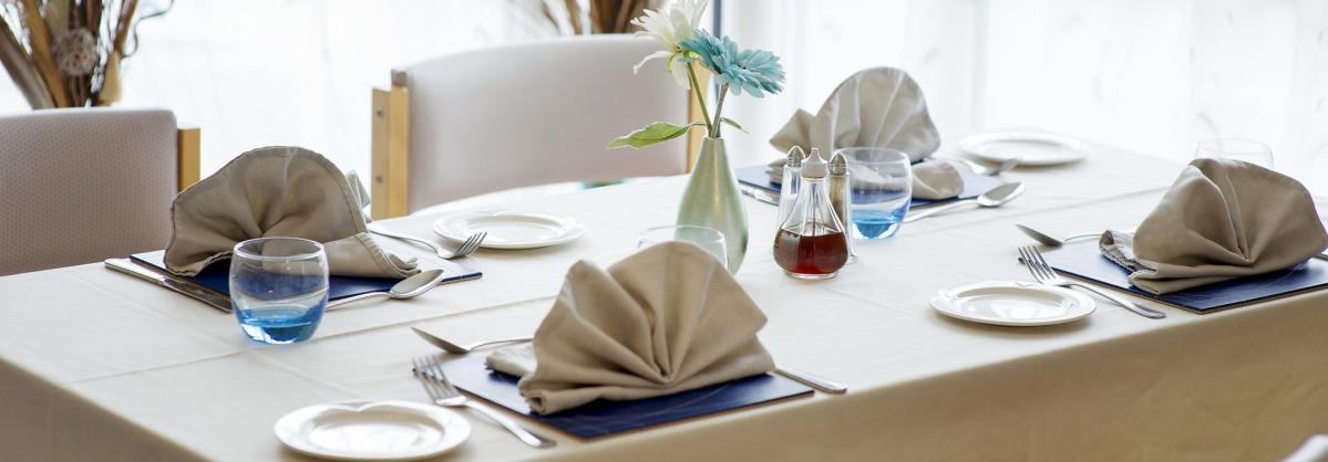 A dining table at Ivydene Residential and Nursing Home set with napkins, glassware and flowers.