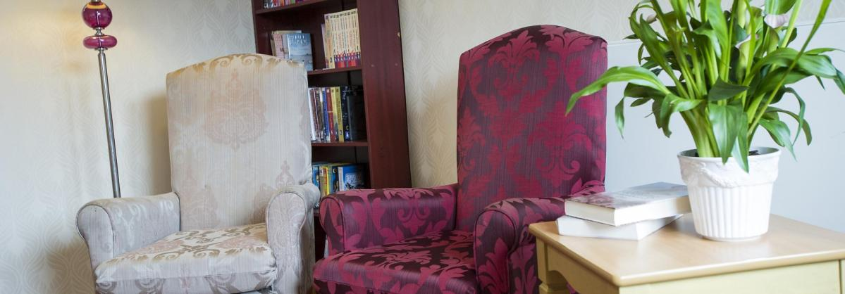Traditional winged-back chairs in the lounge at Lammas House Residential Care Home.