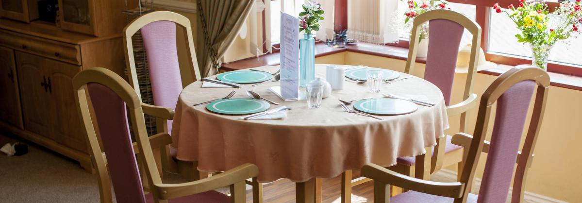 The dining room at Lammas House Residential Care Home has stylish wooden floors and furniture.