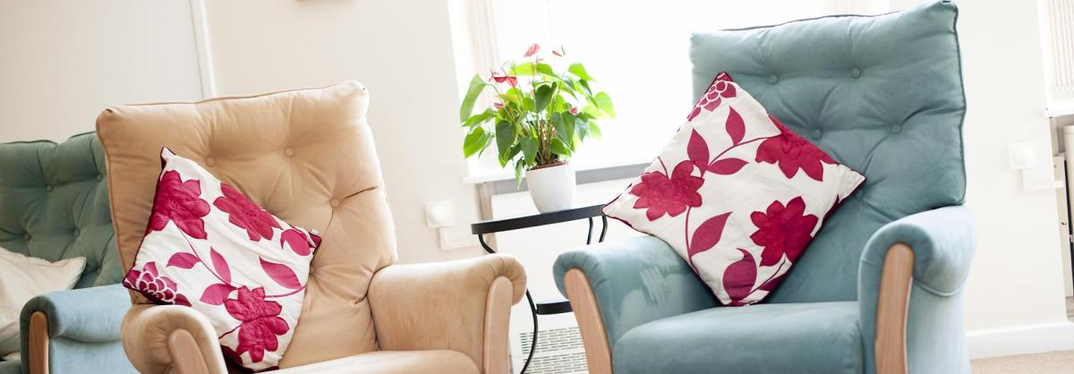The lounge at Orchard House Residential Care Home with soft chairs and floral cushions.