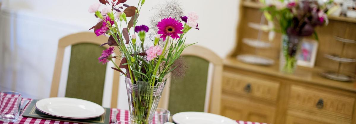 The dining room  at Shaftesbury House Residential Care Home with flowers, dresser and chequered table cloth.