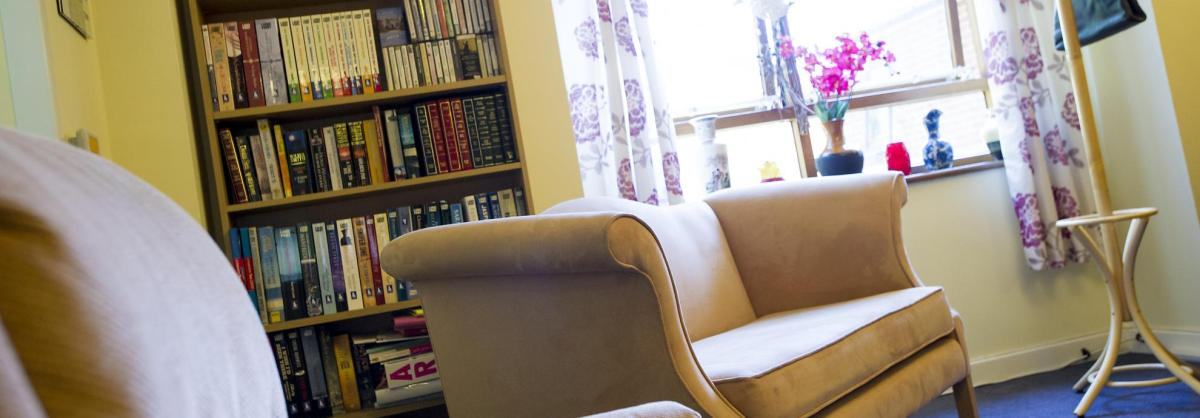 The lounge at Shaftesbury House Residential Care Home with comfy chairs, book shelves and large window.