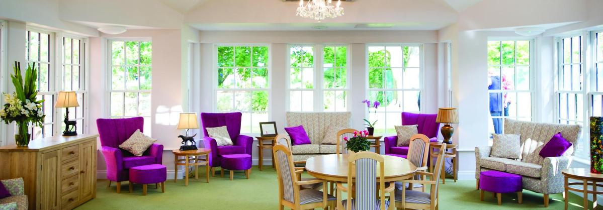 The stunning lounge with high ceilings and chandeliers at Watlington and District Nursing Home.