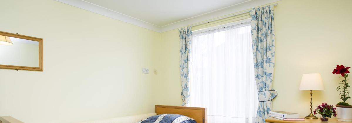 A blue and cream bedroom at Rowanweald Nursing Home.